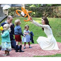 |September 28, 2016| — Catherine, Duchess of Cambridge, Prince William, Duke of Cambridge, Prince George of Cambridge and Princess Charlotte of Cambridge at a children's party for Military families during the Royal Tour of Canada on September 29, 2016 .........CHARLOTTE IS MORE INTERESTED IN HER SWEATER THAN THE BALLOONS...........ccp