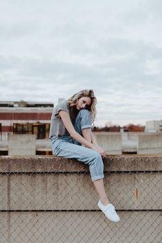 นั่งชันเข่าบนกำแพง ให้พื้นหลังเป็นท้องฟ้า