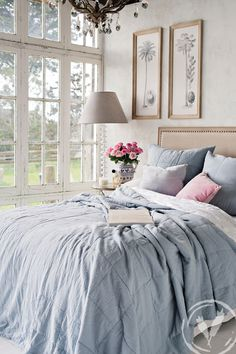A dreamy bedroom, skye quilt and Euros. Sorbet blue and pink cushions, cross stitch jug. Palm and coconut wall art and the amazing Afrique white floor lamp. www.frenchcountry.co.nz