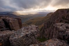 Towering dolerite columns at Devils Gullet plunge into the Fisher River valley and the remote Tasmanian central plateau. The storm engulfing Clumner Bluff (1559m) was directly overhead a few minutes earlier with white out conditions and summer snow. The dolerite columns are over 220m high and form part of the Tasmanian Wilderness World Heritage Area, on the northern rim of the Great Western Tiers. Tasmania, Australia.
