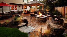 This spacious backyard patio features brown stone throughout, as well as an outdoor sitting area with overhead cover. Dark brown rattan chairs surround a cozy stone fire pit, while a matching dining table with a red umbrella offers a perfect space for a casual outdoor lunch.
