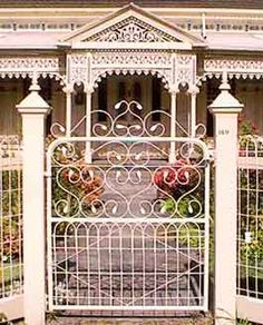 love this whole fence, posts and gate system and that gingerbread trim on the house too