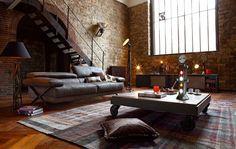 table basse style industriel en bois massif et à roulettes, tapis bariolé et canapé en cuir gris dans le salon
