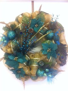 This beautiful, glitzy eye catching Christmas wreath is made from gold deco mesh and is adorned with peacock decor galore! I added glittery