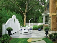 Adding a decorative lattice fence accent not only establishes an elegant backdrop, but also brings the space together with form and function. A white scalloped lattice fence with a keyhole gracefully stands in front of feathery evergreens, giving the space definition and creating a focal point. Tip: White was chosen for this setting because it provides a striking contrast to the dark evergreen vegetation, enhancing the visual appeal. Additionally, the same material was repeated for an arched…