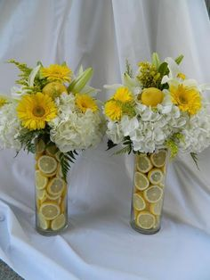 I wish these photos were scratch 'n sniff. Two tall vases filled with sliced lemons and topped with hydrangea, white asiatic lilies, yellow mini gerbs, solidago and fresh whole lemons!