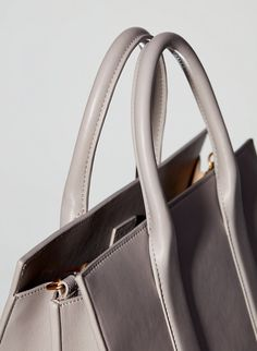 This shoulder bag features bonded leather construction for a clean look and feel. It has a detachable, adjustable cross-body strap. Bonded Leather, Leather Handle, Fashion Bags, Leather Shoulder Bag, Dust Bag, Fitness Models, Sneakers, Clothing, Tennis