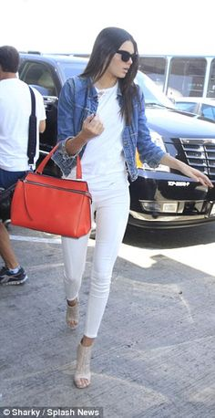 Runway girl: The brunette beauty teamed her casual off-duty look with large black aviators and a gorgeous bright red designer handbag