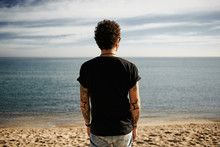 Brutal man with tattoos on beach standing in sand looking at sea