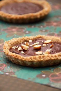 Tartelettes chocolat noisette  Pour la pâte à tarte sablée sans beurre : •70 g de poudre de noisette •50 g de sucre complet •100 g de farine de quinoa •70 g de fécule de pommes de terre •1 pincée de bicarbonate de sodium •80 g de purée de noisette •70 g d'eau •1 jaune d'œuf Pour la ganache au chocolat : •200 g de chocolat noir dessert (min. 60% de cacao) •3 c.a.s de crème de soja (ou amande) •1 blanc d'œuf Pour la décoration (facultatif) : Quelques noisettes concassées
