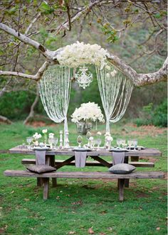 So romantic! I love the rustic table paired with the chandelier and white flowers!