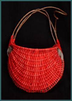 Red Door Pouch, a small pocket wallhanger woven by basket artist and master weaver Tina Puckett, handle and frame of bittersweet, adorned with feathers