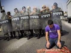 Photographic Print: Palestinian Worshipper Prays Outside Jerusalem's Old City While Israeli Forces Stand Guard : 24x18in