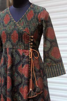 a mughal-inspired anghrakha wrap with pintucked yoke and dori with fabric tokri. main fabric: cotton, handblock printed using natural dyes in ajrakh tech Printed Kurti Designs, Tunic Designs, Kurta Designs Women, Kurti Neck Designs, Dress Neck Designs, Kurta Cotton, Cotton Tunics, Pakistani Dress Design, Pakistani Outfits