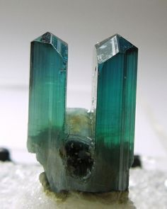 A 1.5 cm tall specimen with two terminated Indicolite crystals being separated by a smaller horizontal crystal.  The Indicolite is mostly ge...