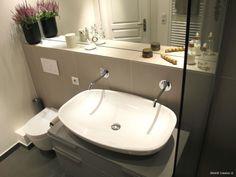 Grande vasque blanche avec deux robinets posée sur un meuble de rangements