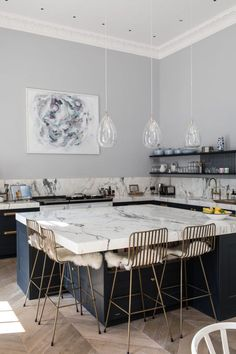 Gorgeous kitchen with dove grey walls, huge marble island, and gorgeous gold stools