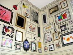 walls covered in hand drawn frames and moldings. The artist hung some of her children's art, painted the frames with black craft paint, and used Sharpies to do the detail work. DIY?