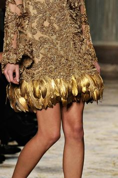 Gold Dusted feathers on the hem of a cocoa brown re embroidered and Crystal beaded lace.