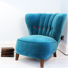 For stylish relaxation, why not cosy-up with this beautiful one of a kind vintage armchair? Its elegantly curved back and fully box-sprung seat shows the true quality of this unique piece.    Recovered in a striking blue Boston Velvet from Casamance with vibrant hot fuchsia accent buttons, this armchair has had a full back-to-the-frame restoration by a professional upholster and is fully compliant with domestic fire regulations.