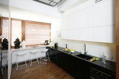 Elegancką kuchnię urządzono w duecie bieli i czerni. Projekt: Monika i Adam Bronikowscy. Fot. Bartosz Jarosz.