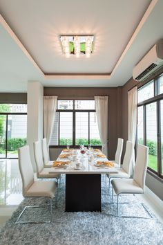 Very simple white and dark grey dining room design.  Table leg is dark grey and the top is white surrounded by six white dining chairs sitting on blue rug.