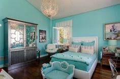 An elegant teenage girl's room in Tiffany blue, featuring a suspended chair, mirrored armoire, and a small bench at the foot of the upholstered bed frame.