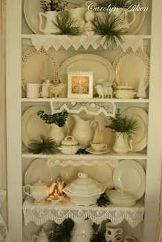 love the scraps of crocheted lace on the shelves, the white ironstone dishes, the touches of greenery and the flicker of light on these shelves....