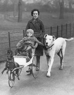 1932: A small girl in a push chair modelled on a horse-drawn carriage, out for a stroll in Hyde Park, London, with her mother and a Great Dane