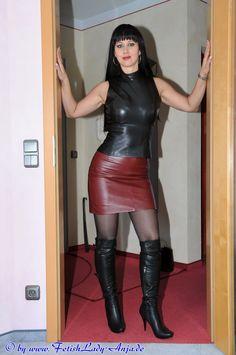 Dame en boléro de cuir noir moulant sa poitrine, jupe de cuir rouge grenat, bottes noires. Cheveux noir, rouge à lévres, mains contre l'encadrement d'une porte.