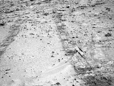 """This view obtained on July 9 from the left Navigation Camera (Navcam) of NASA's Mars Rover Curiosity looks back at wheel tracks made during the first drive away from the last science target in the """"Glenelg"""" area."""