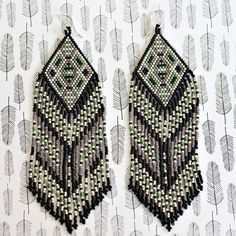 Another new design of beaded earrings! This is one of my latest creations of native American inspired fringe earrings made with seed beads. This particular pair is a bold & striking mix of a deep matte black, matte lavender, matte sage green, an off white and silver tones. I loved this color scheme so much, I made a pair for myself :) These beaded earrings are long but lightweight for their length and are comfortable to wear all day. The fringe on the earrings sways beautifully when worn and…