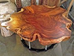 Custom made cross cut monkeypod slab wood natural edge coffee table on salvaged steel gear base.  By Impact Imports.