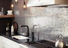 Such a cool kitchen … stainless metal mosaic tiles, aged bronze cage pendant lights, an adjoining wall painted chalk-board black + counter, tapewear also in black (like the added contrast of the recla