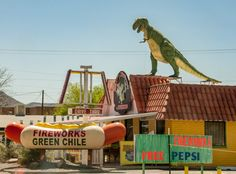 No, you're not seeing things. That is a dinosaur marauding across the roof of a business selling both fireworks and chile.