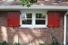 Red bi-fold exterior shutters made for this customer who wanted properly sized and functional shutters. Shutter hardware includes tiebacks, hinges, pintels, locks and pull rings.
