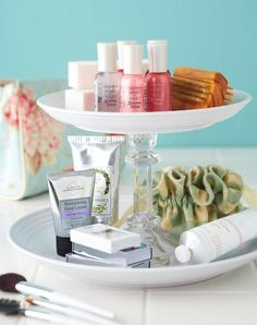 A cake stand or two plates glued to a candlestick elevate tiny bottles and tubes on a bathroom counter.