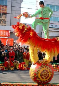 Chinese New Year festival parade. Dancing mythical creature Lion on a ball with boy