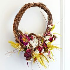 Add fall flowers to a grapevine wreath to create this easy decor piece for your walls or door