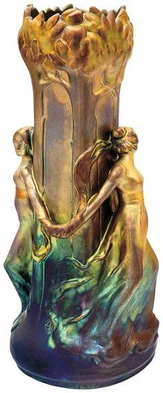 Zsolnay VÁZA, KÉT NŐVEL, 1900  Fazonszám: 6101, Magasság: 42,5 cm Jelzés: domború körpecsét és Mack Lajos jelzése; egy makk a tárgy oldalán  Formaterv: Mack Lajos Porcelánfajansz, reliefmintázattal, ráillesztett figurákkal. Opak és transzparens, fémszínű, márványosan összefolyó eozinmázas festés, felülete savmaratott. VJ17/L1,2