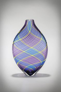 Multicolor Cane Vessel in Violet by Michael Hermann and Gina Lunn. Beautiful cane patterns lined in specific colors to create a dazzling optical effect when the viewer looks through the piece. The artists first create patterned glass rods called cane, cut them into individual cross-sections, and lay out a specific color pattern. This pattern is then twisted over a core of clear glass. Primary colors used in this vessel are violet, blue, and amber. The effect is stunning.