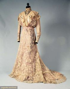 "BELLE EPOCH LACE TEA GOWN, c. 1900 2 piece ecru cotton net w/ Brussels lace applique & tambour embroidered lace, long sleeves, high neck bodice, front w/ cream satin trim & diamante oval brooches, trained skirt w/ deep hem flounce, B 38"", W 24"", Skirt L 44""-57"", (satin damaged, dress dingy, 5"" rip in hem edge at back of train, lavender silk linings completely shredded) fair, lace good. BMCC"