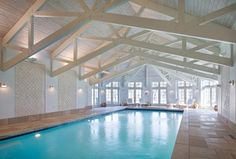 Contemporary Swimming Pool with Indoor pool, travertine tile floors, Exposed truss ceiling, Transom window, French doors