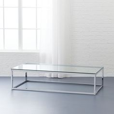 Shop smart glass top coffee table.   Open box construction of slick polished chrome tops out in glass clear, sheer.  Coffee table sports genes just 12 inches off the floor.