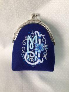 Monedero con iniciales entrelazadas. Bordado en tonos azules.