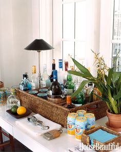 """Designer Tom Scheerer corralled barware and liquor bottles in a basket with matching napkin caddy in a Vero Beach, Florida house: """"I put it between the living and family rooms. Bars express welcome and conviviality, and I like them out in the open.""""   - HouseBeautiful.com"""