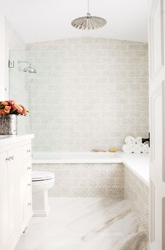 Gleaming white bathroom with subtle pattern in tile on wall of shower and bath // orange and red roses on sink