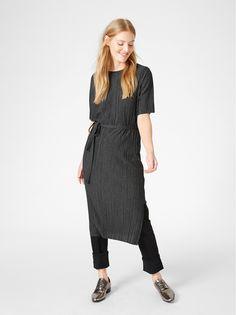 7f5820da9105 Den här plisserade klänningen har en elegant stilren känsla. Den raka  passformen och bältet som