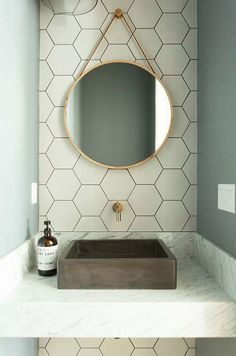 Well styled contemporary powder room features a nook fitted with a round gold mirror hung from cream hexagon backsplash tiles over a marble floating sink vanity. Tiny Powder Rooms, Modern Powder Rooms, Bathroom Interior, Modern Bathroom, Small Bathroom, Contemporary Bathroom Mirrors, Small Toilet Room, Bathroom Marble, Powder Room Decor