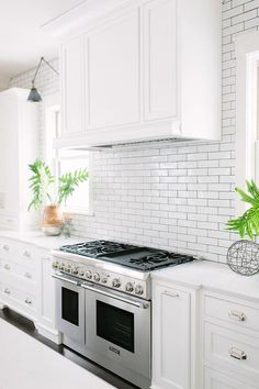 A stainless steel dual range is fixed between white cabinets adorning polished nickel cup pulls and a white quartz countertop fixed against white linear backsplash tiles framing windows located on either side of a white wainscot hood.